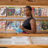 """Stephanie Toliver in a comic book store reading an issue of """"Ironheart"""""""