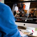 Man watches video with captions on Mac computer