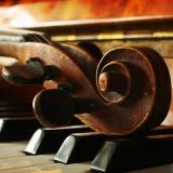 Violin head lying across piano keys
