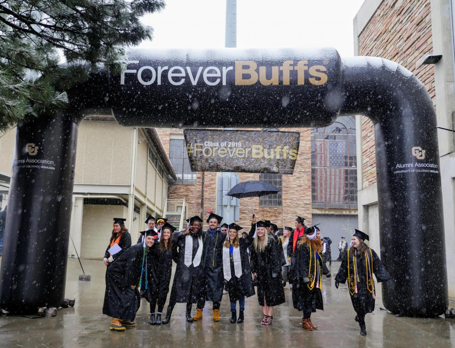 Graduates pose for a photo under a blow-up Forever Buffs arch