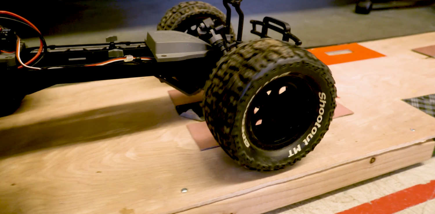 A remote control car drives across a prototype of the wireless charging system.
