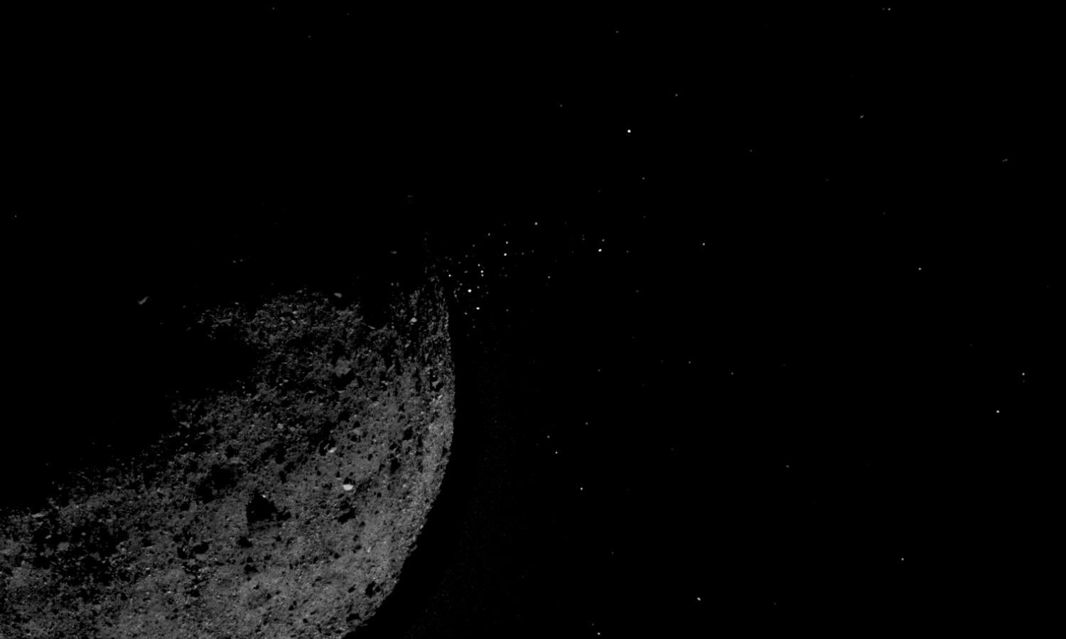Image of the asteroid Bennu with small bits of material jumping off into space.
