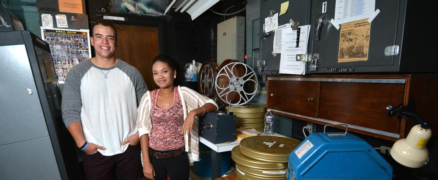 Adam Elbeck and Melina Dabney pose in the CU Boulder film lab with stacks of movie reels