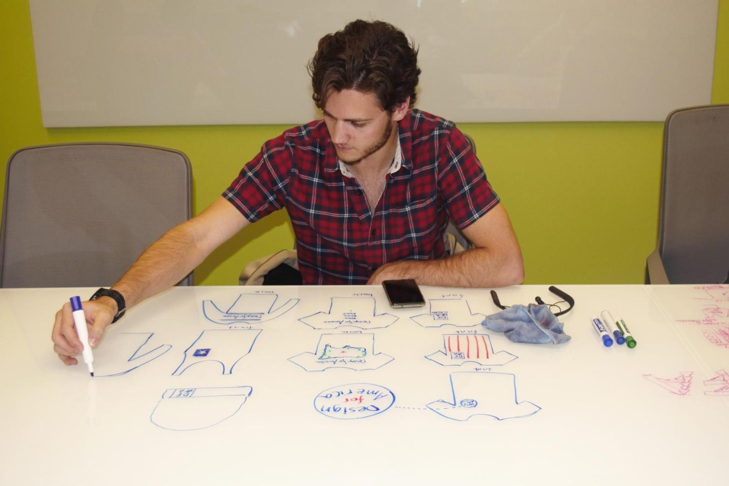 Design for America student sketches ideas on dry erase board