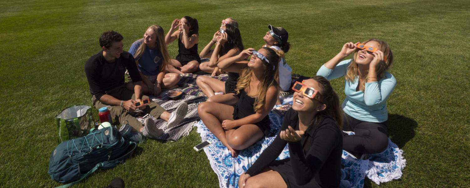 Students sit on campus watching the Great American Eclipse