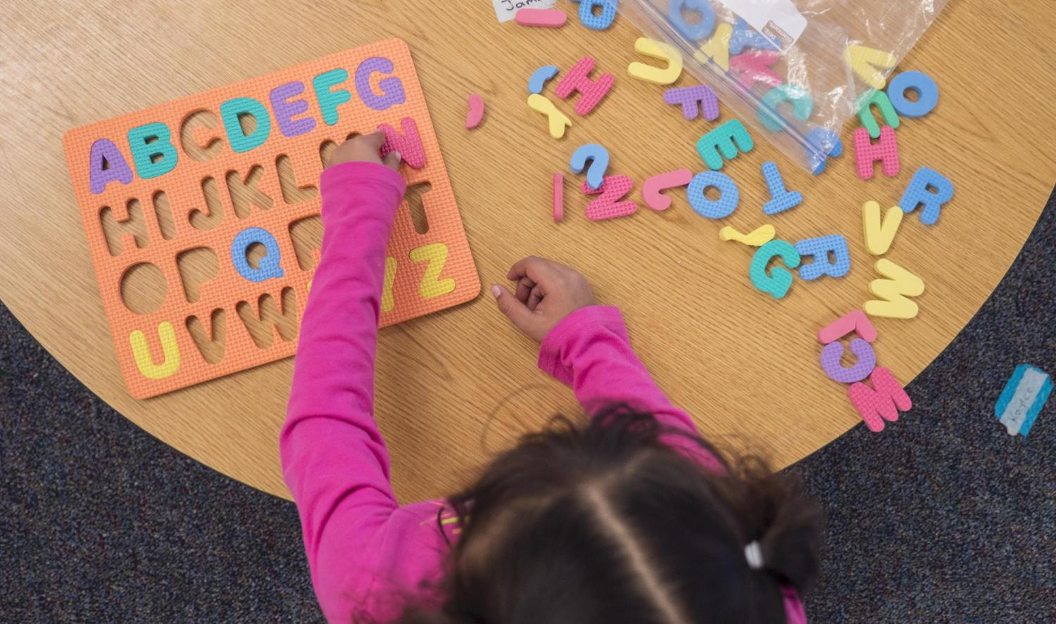 Child playing with an alphabet puzzle