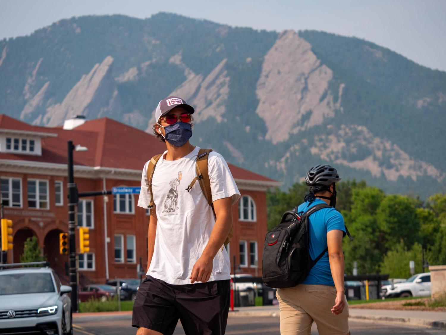 Student walking near campus while wearing a mask.