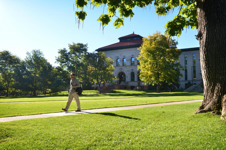 Campus community member walks across Norlin Quad