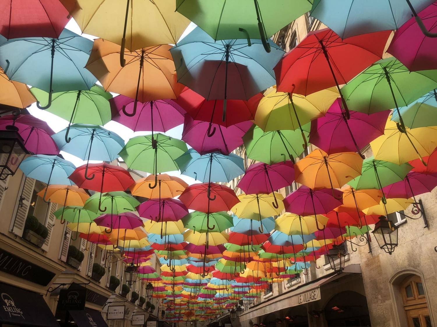 Colorful umbrellas cover a Paris street