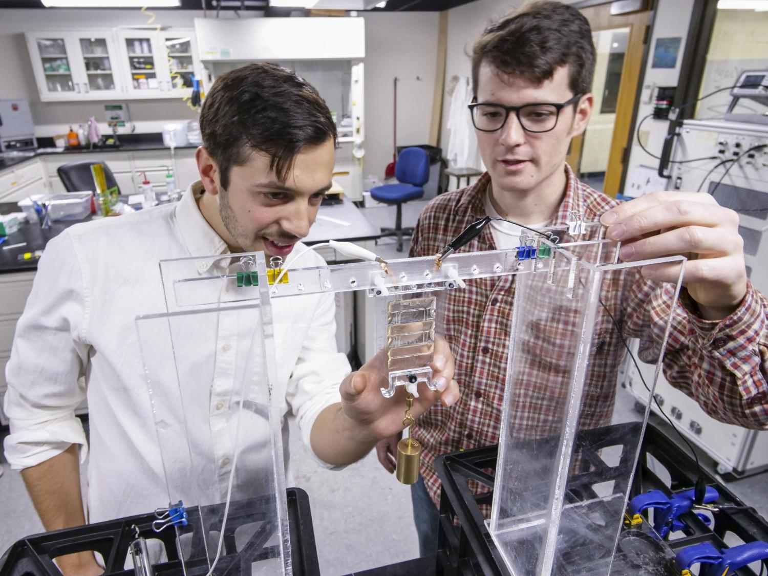 "Nick Kellaris, a materials science and engineering graduate student, left, and Mechanical engineering graduate student Eric Acome, looks over liquified artifical  ""muscle"" or soft robot material in the Keplinger Research Lab."