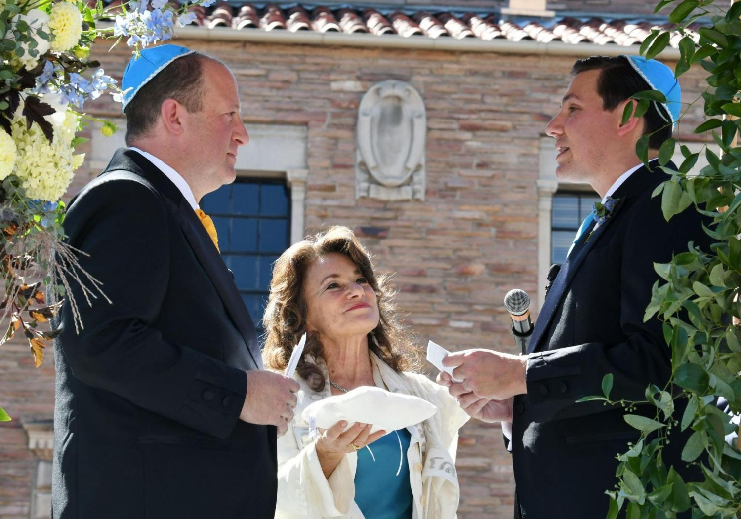 Jared Polis and Marlon Reis face each other as an officiant looks on.