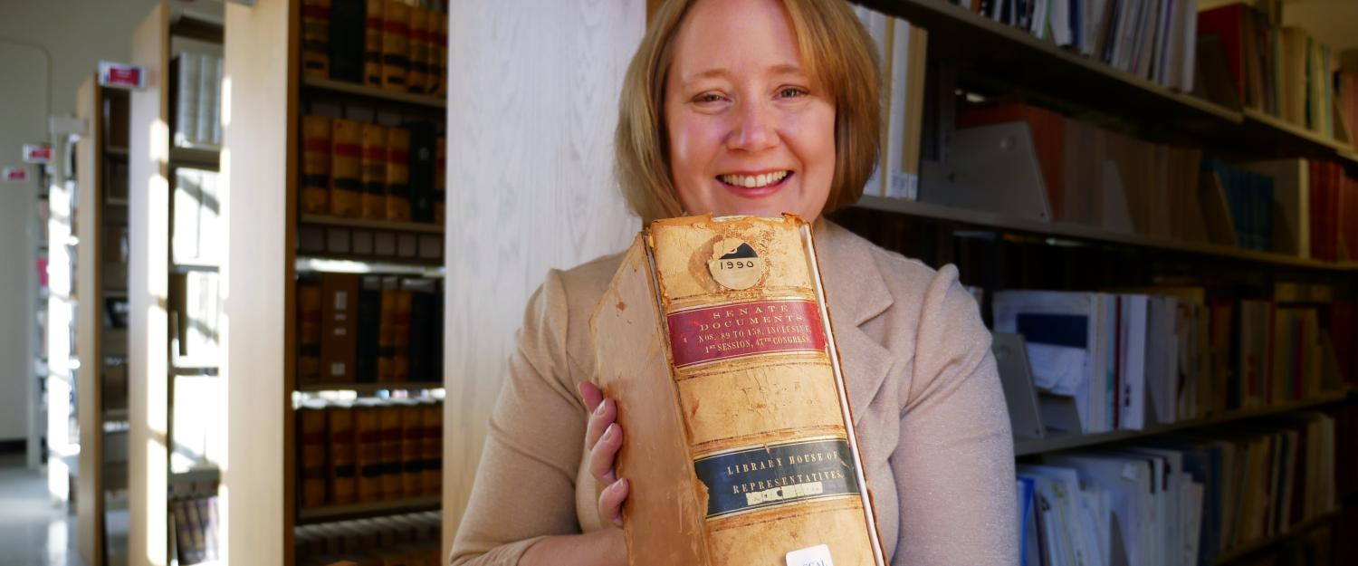 Kate Tallman is pictured holding an old thick volume of Senate documents with bookshelves behind her in Norlin Library.