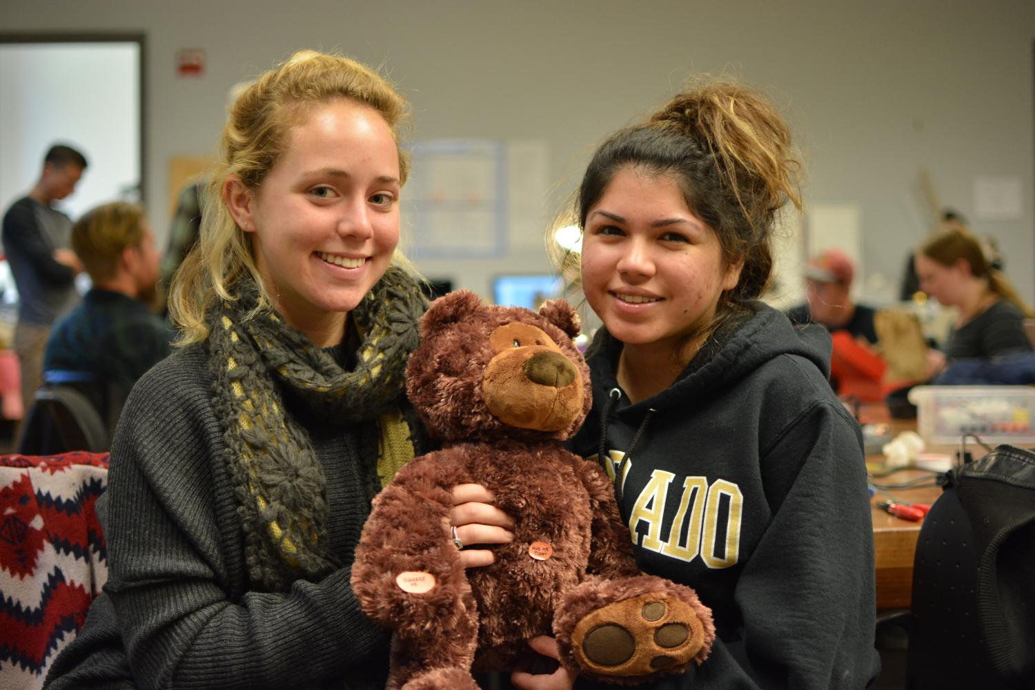 "Marla Bernstein and Carolyn Castanon, hold their teddy bear, ""Chill Out Carly""between them."