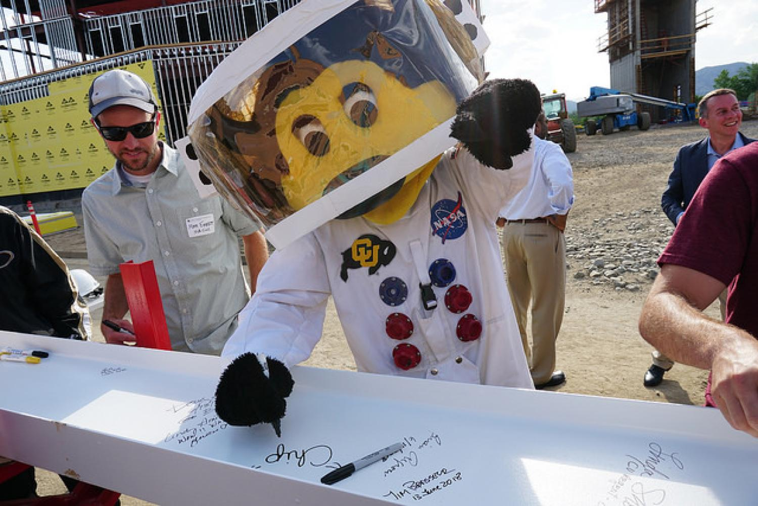 Chip signs a beam to be added to the new aerospace engineering building