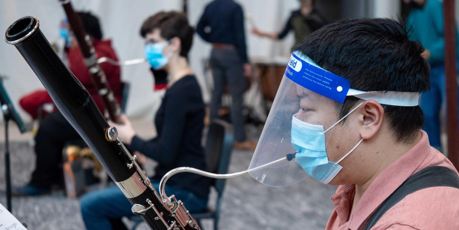 Man plays a musical instrument while wearing a face shield and mask.