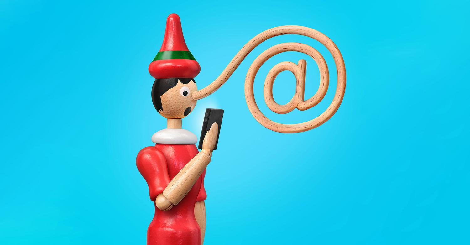 "A Pinocchio doll reading a smart phone, with his elongated nose in the shape of an ""@"" symbol."