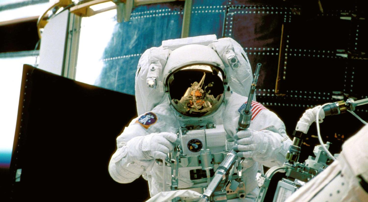 Astronaut dons a suit to work on the Hubble Space Telescope