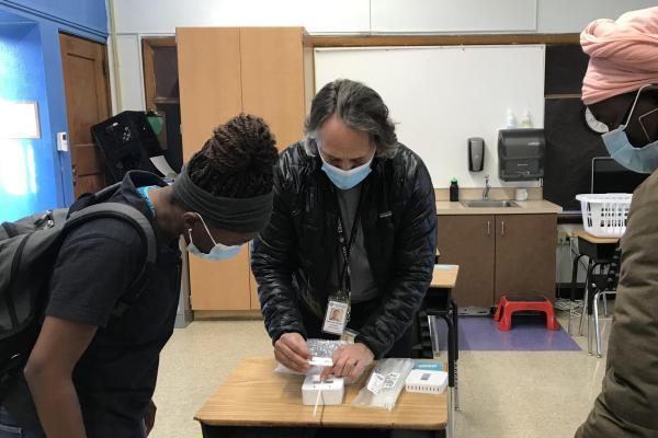 Professor Mark Hernandez demonstrates the installation process for the classroom air quality remote sensors to CU Boulder student volunteer technicians Christiane Nitcheu and Sylvia Akol. (Photos courtesy Anna Segur)