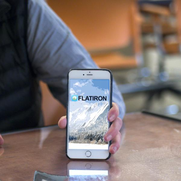David Meyer holds his phone to display the Flatiron Chat app on screen