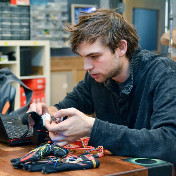 """Technology, Arts and Media student Kristof Klipfel works at a computer with his """"piano gloves"""""""