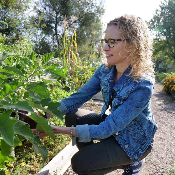 Professor Jill Litt looks over an eggplant at a community garden next to Regis University in Denver
