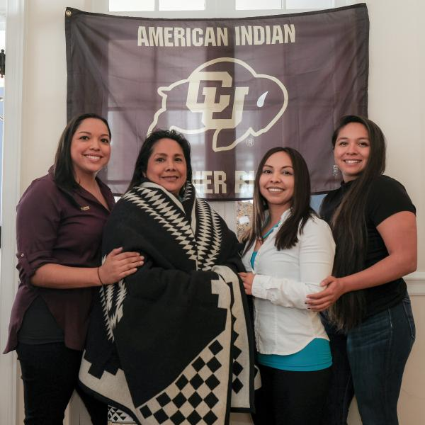 "Patrita ""Ime"" Salazar wears a ceremonial ""Los Ojos"" wool blanket as she poses with her daughters, left to right, Kalee, Tachara and Cibonet."