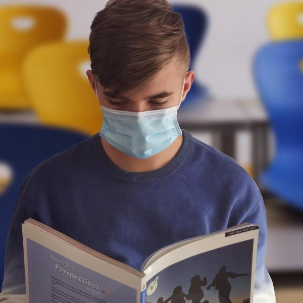 Student reading while wearing mask