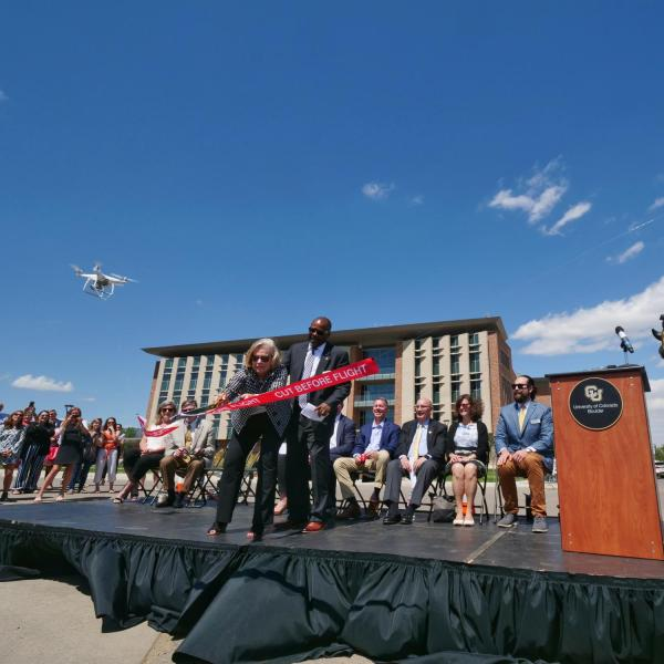 Ann Smead, left, and Brian Argrow, chair of the aerospace engineering department, cut a ribbon held by drones at a ceremony at the new Aerospace Engineering Sciences Building at CU Boulder. (Photo by Glenn Asakawa/CU Boulder)