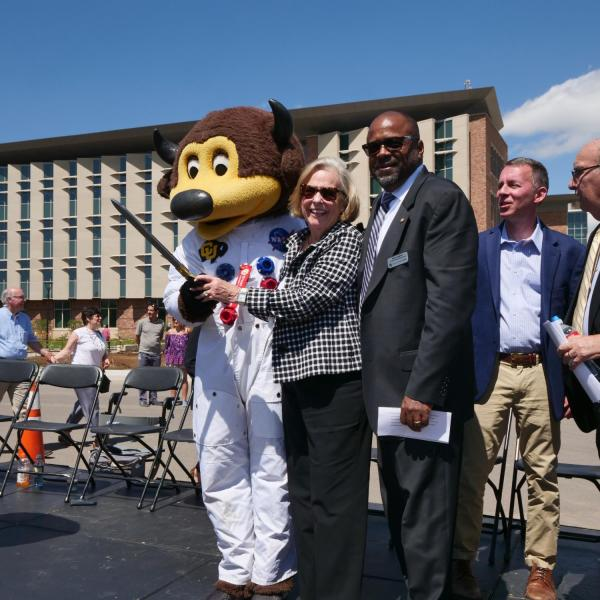 Ann Smead, center, and Brian Argrow, chair of the aerospace engineering department, right, pose with Chip following a ribbon-cutting ceremony at the new Aerospace Engineering Sciences Building at CU Boulder. (Photo by Glenn Asakawa/CU Boulder)