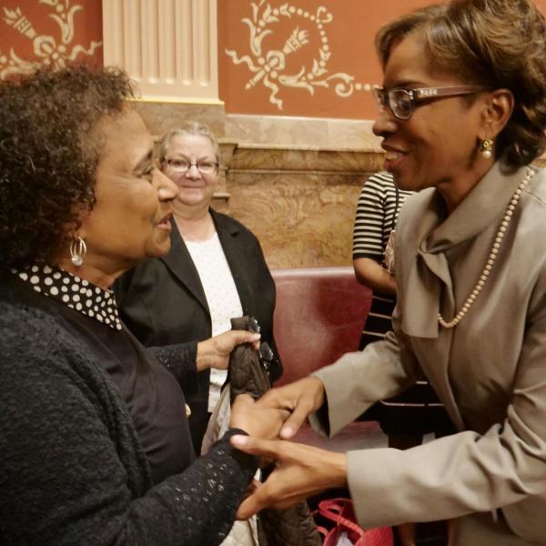 State Senator Rhonda Fields, right, greets CU Professor Polly McLean before providing a tribute of Lucille Buchanan.