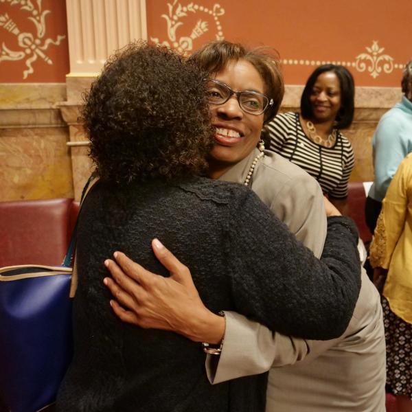 State Senator Rhonda Fields, right, hugs CU Professor Polly McLean before providing a tribute of Lucille Buchanan.