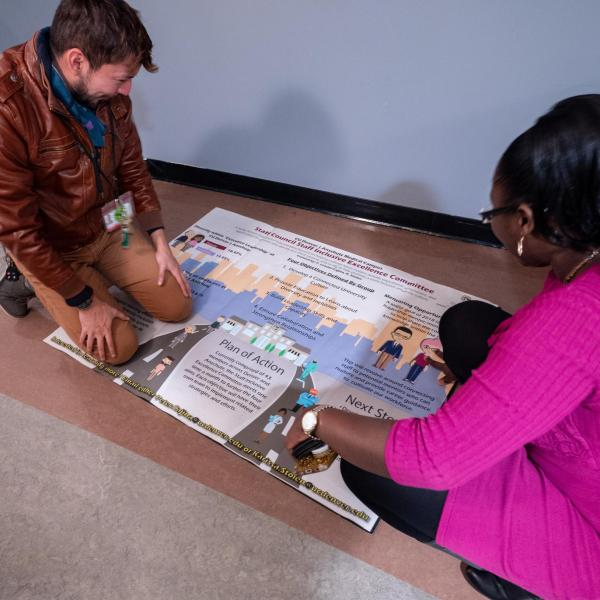 Staff put the finishing touches on a Staff Council-produced poster during the second day of events. Photo by Glenn Asakawa.