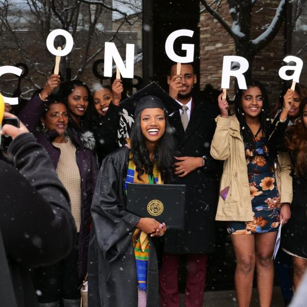 Graduate poses with family for photo after Integrative Physiology recognition ceremony