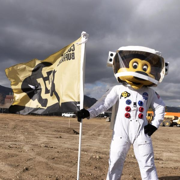 Mascot Chip plants the Colorado Buffaloes flag at the new aerospace building grounds
