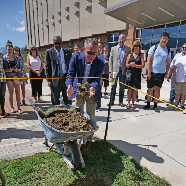 Dean Bobby Braun tosses dirt on a time capsule in front of CU Boulder's new Aerospace Engineering Sciences Building.