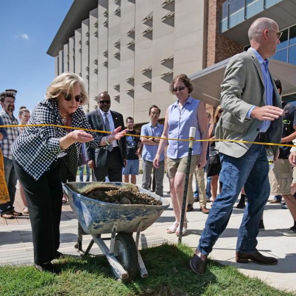 Donor Ann Smead tosses dirt on a time capsule in front of CU Boulder's new Aerospace Engineering Sciences Building.