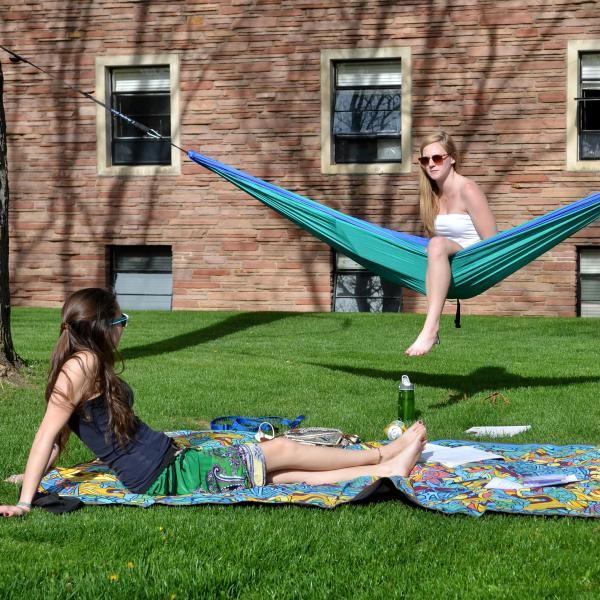 Students lounge outside in hammocks, on blankets