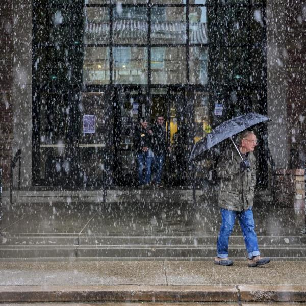 A person ventures out into snowfall with an umbrella. Photo by Patrick Campbell.