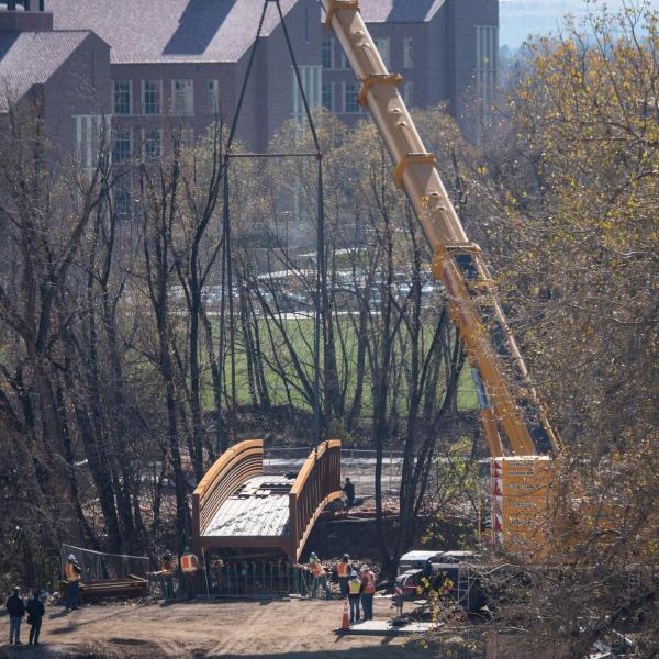 Workers use a mobile crane to place a 33-ton bridge over Boulder Creek on East Campus. Photo by Glenn Asakawa.