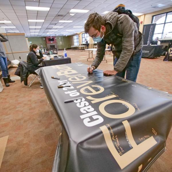 Students sign the Class of 2021 banner and pick up regalia at the 2021 Gear Grab event. (Photo by Casey Cass/University of Colorado)