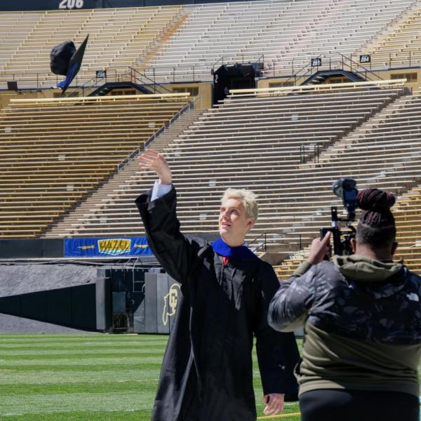 Alexander Whiteman tosses his cap for a formal photo on Folsom Field at Folsom Field during CU Boulder's Graduate Appreciation Days events on April 23, 2021. (Photo by Glenn Asakawa/University of Colorado)