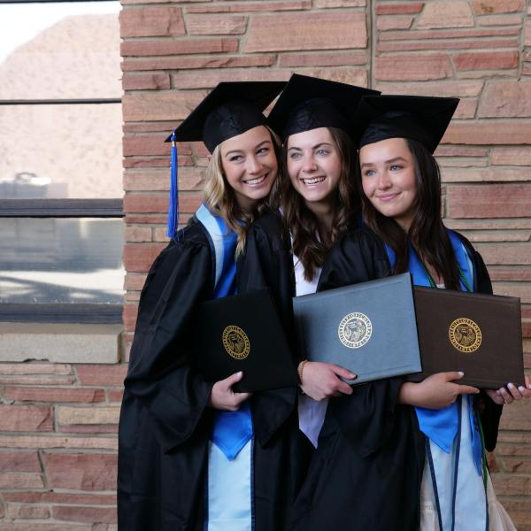 Accounting graduate Alexa Reber, left, political science and anthropology graduate Katie Burns, center, and finance graduate Claudia Hall, right, pose for a friend's photo during CU Boulder's Graduate Appreciation Days events. (Photo by Glenn Asakawa/University of Colorado)