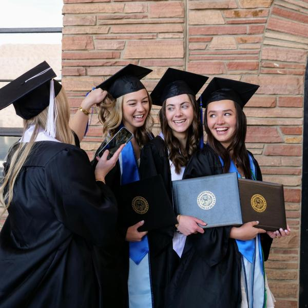 Accounting graduate Alexa Reber, second from left, political science and anthropology graduate Katie Burns, second from right, and finance graduate Claudia Hall, right, pose for a friend's photo during CU Boulder's Graduate Appreciation Days events. (Photo by Glenn Asakawa/University of Colorado)