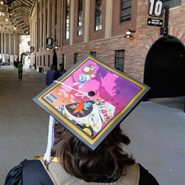 A graduate sports a creatively-decorated cap during CU Boulder's Graduate Appreciation Days events on April 23, 2021. (Photo by Glenn Asakawa/University of Colorado)