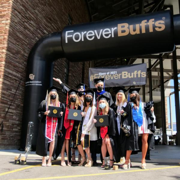 Graduates gather for a group shot after getting their individual portraits taken on Folsom Field during CU Boulder's Graduate Appreciation Days events. (Photo by Glenn Asakawa/University of Colorado)