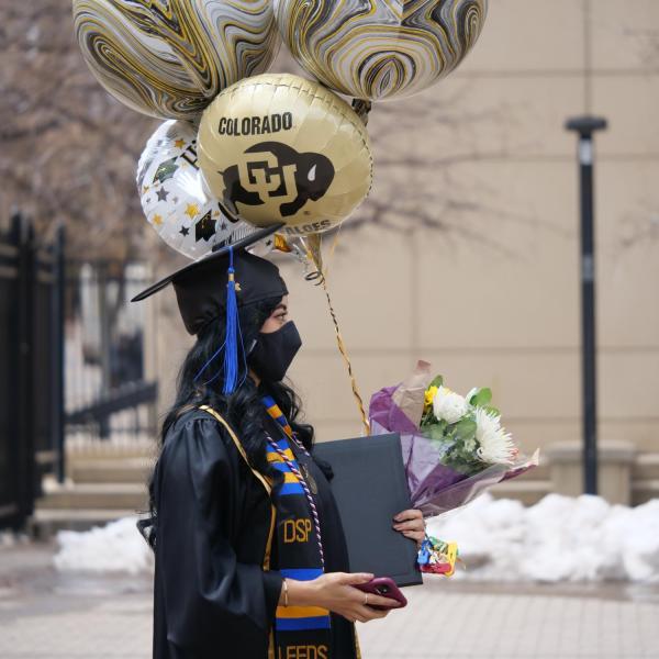 Adilene Garcia Aniles carries an armload of celebratory accessories during CU Boulder's Graduate Appreciation Days events. (Photo by Glenn Asakawa/University of Colorado)