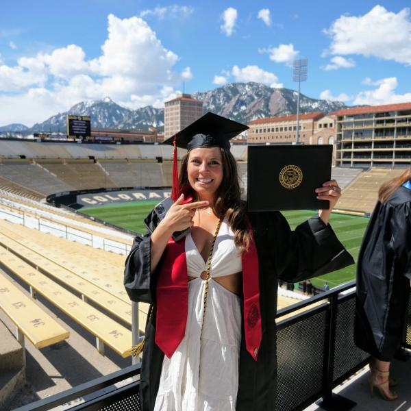 Journalism graduate Kiely Weshoff points to her diploma board after getting her photo taken in Folsom Field during CU Boulder's Graduate Appreciation Days events on April 23, 2021. (Photo by Glenn Asakawa/University of Colorado)
