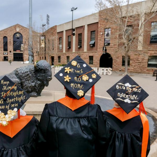International chemical engineering graduates from Malaysia (from left) Nur Alwani, Adam Izz Khan, and Nur SyrahHirah, display their inspirational messages on their caps during CU Boulder's Graduate Appreciation Days events. (Photo by Glenn Asakawa/University of Colorado)