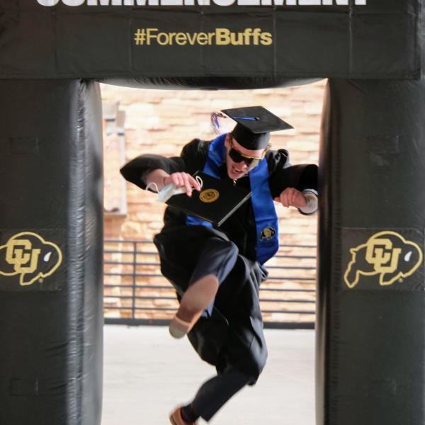 Matt Wolff leaps through an inflatable photo frame during CU Boulder's Graduate Appreciation Days events. (Photo by Glenn Asakawa/University of Colorado)