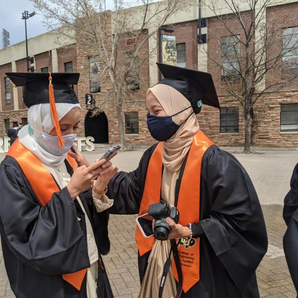 International chemical engineering graduates from Malaysia (from left) Nur Alwani, Nur SyrahHirah, and Adam Izz Khan finish a long distance chat with their families during CU Boulder's Graduate Appreciation Days. (Photo by Glenn Asakawa/University of Colorado)